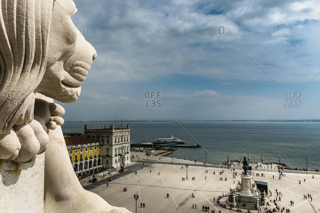 Lisbon, Portugal - April 16, 2014: Plaza of Commerce with pedestrians and statue of stone lion under cloudy sky in Lisbon, Portugal