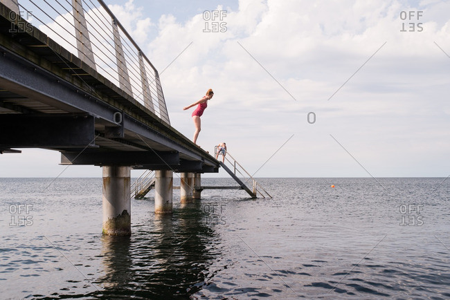 Woman about to jump off swimming pier