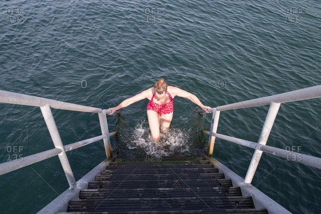 Woman climbing up stairs out of water