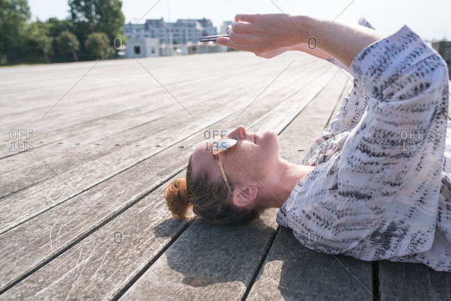 Woman lying on boardwalk while using smartphone