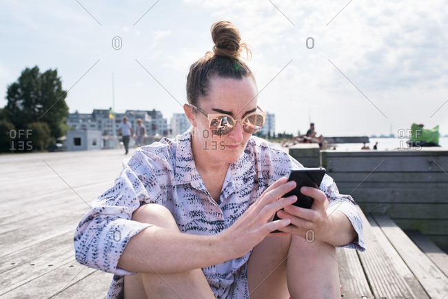 Woman with sunglasses and hair in bun using smartphone