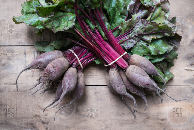 Bunches of red beets on wooden surface