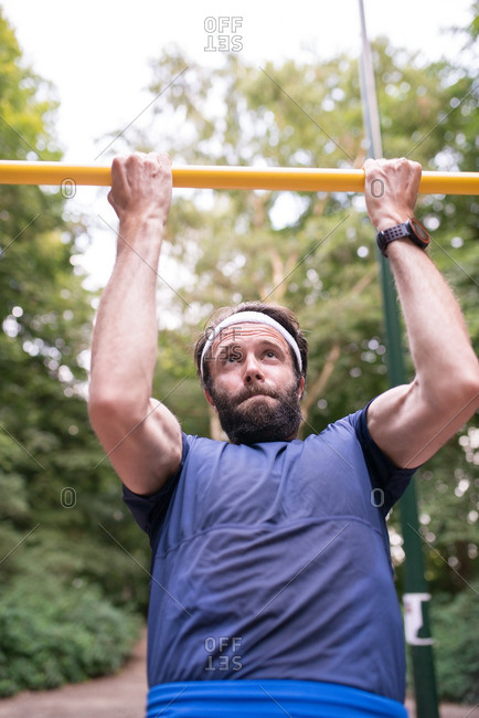 Man doing pull-ups for exercise outdoors