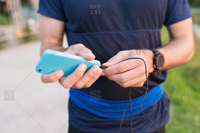 Man plugging headphones into smartphone