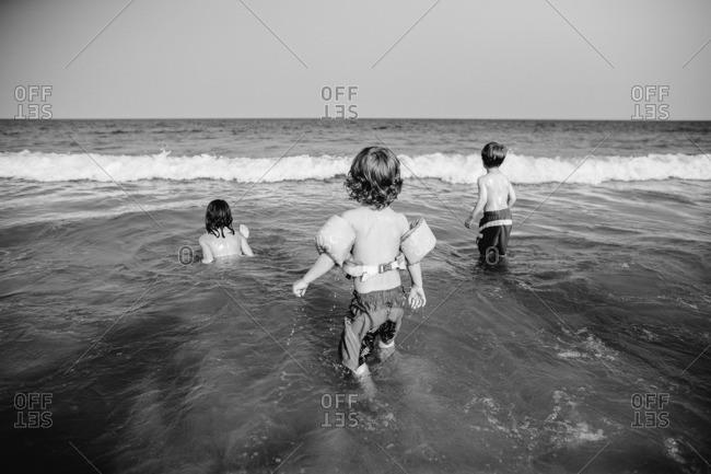 Three children playing in ocean