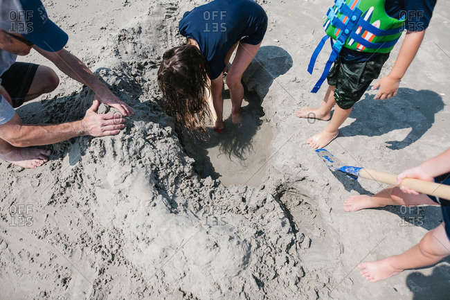 Overhead view of family digging in sand on beach