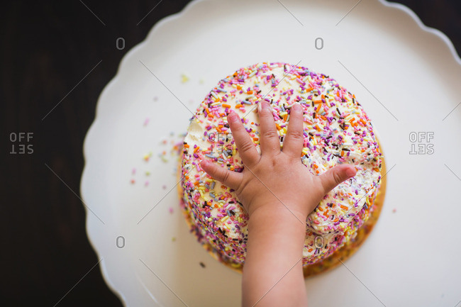 Toddler's hand grabbing a cake