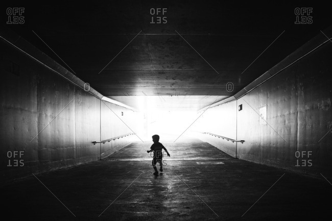 Young child running through tunnel