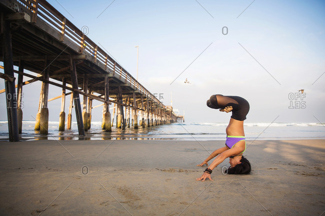 Woman in inverted lotus position on beach