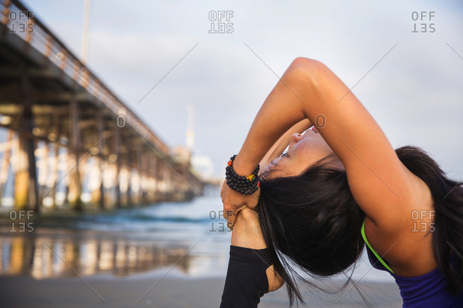Woman bringing her foot to back of her head in beach yoga