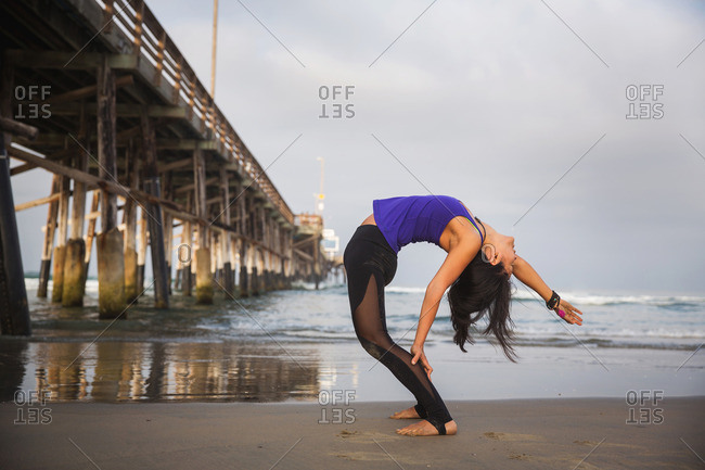 Woman doing a back bend on beach