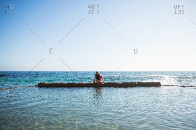 Woman doing yoga on barrier in ocean