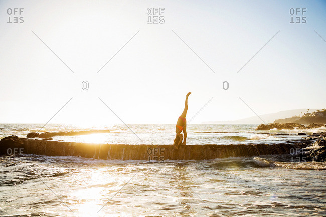 Woman practicing yoga on stone wall in ocean