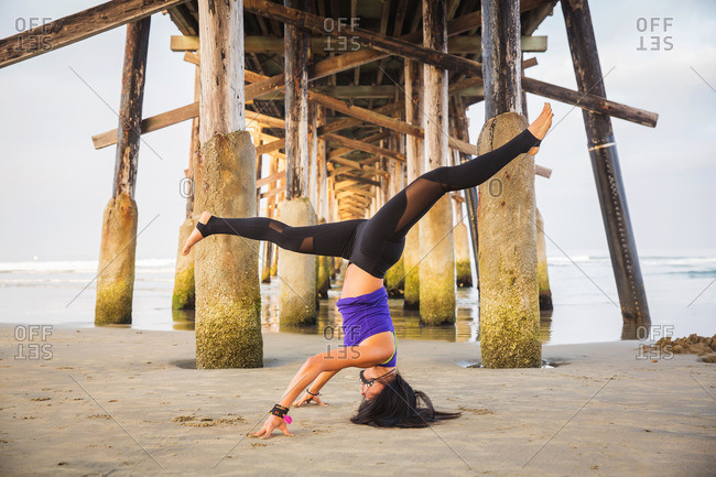 Woman doing headstand on beach below pier