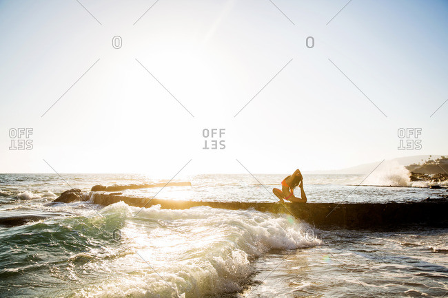 Woman doing yoga in ocean at sunset