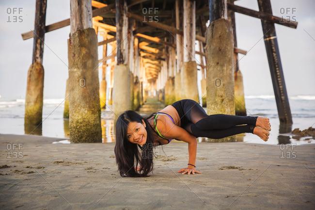 Smiling woman doing yoga on beach beneath pier