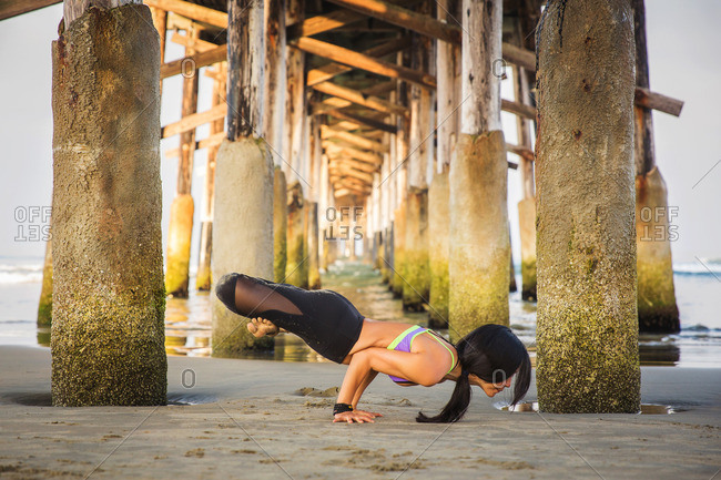 Woman supporting whole body on hands in yoga on beach