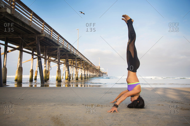 Woman doing headstand on beach next to pier