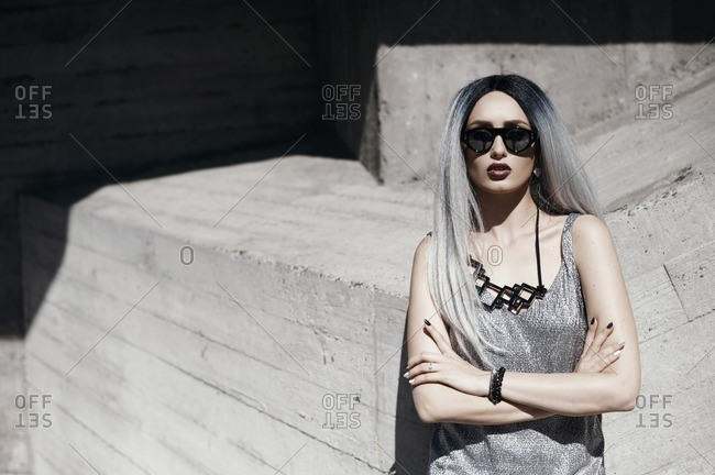 Fashion portrait of woman with gray hair standing against concrete building