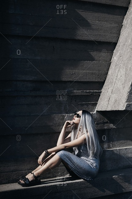 Model with gray hair sitting against concrete wall
