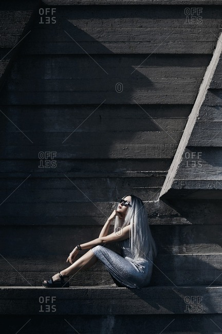 Woman with long silver hair posing against concrete wall background