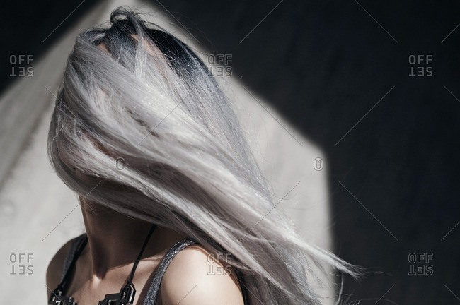 Woman with long silver hair blowing over her face