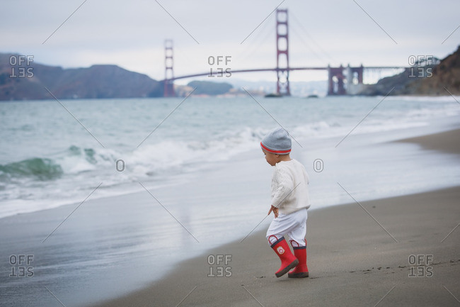 Toddler in red boots on beach with Golden Gate Bridge