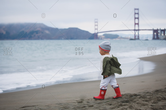 Baby in red boots on beach with Golden Gate Bridge in background