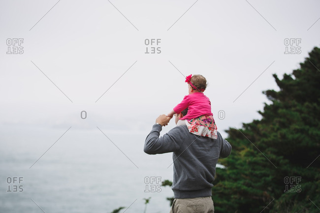 Father overlooking sea with baby daughter on his shoulders