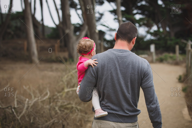 Man carrying infant daughter on hiking trail