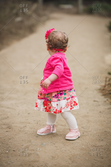 Baby girl in pink sweater and dress turns back to look behind her