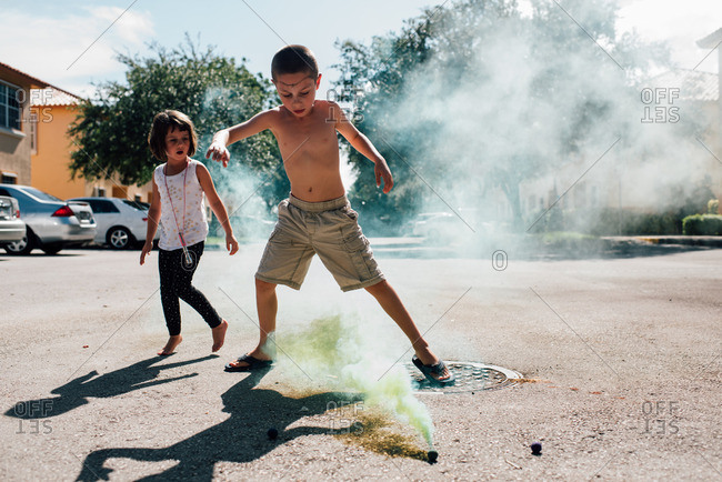 Boy and girl playing with smoke bomb outside
