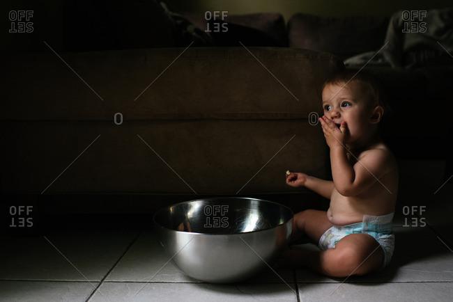 Baby feeding self from big silver bowl on floor