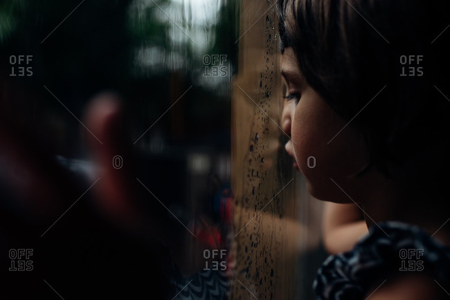 Girl with face pressed against window looking out at rain