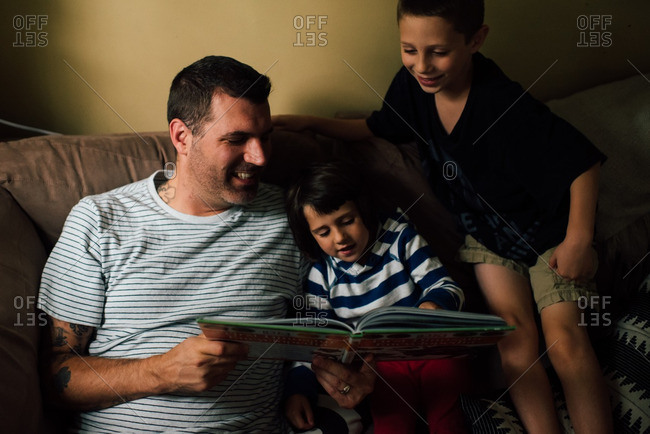 Father reading book to son and daughter