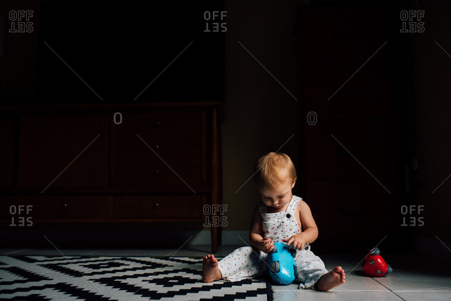 Baby girl playing with blue and red toy cars on floor