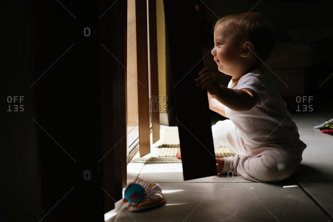 Baby playing with vertical blinds by window