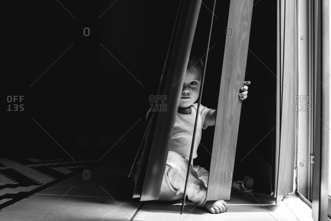 Baby hiding in vertical blinds by window