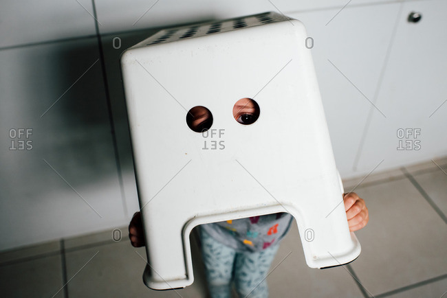 Child peeking out holes in stool on head