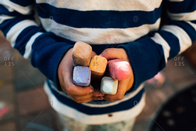 Child's hands holding colorful sidewalk chalk