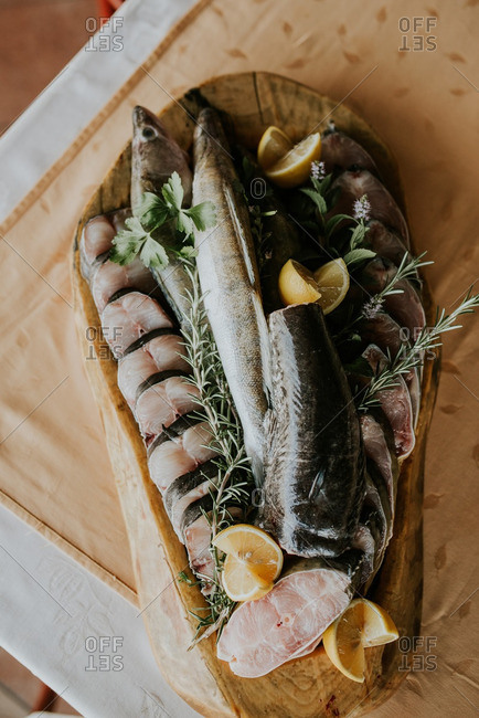 Overhead view of raw fish with rosemary and lemon