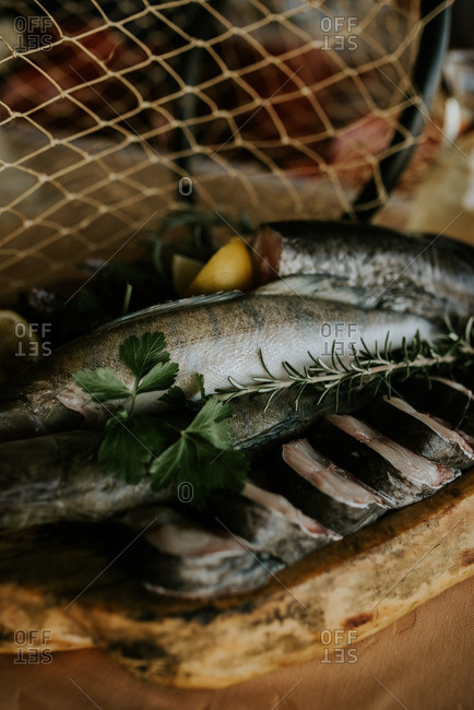 Close up of raw fish with rosemary and lemon