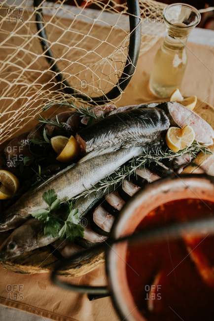Raw fish with herbs and lemon next to a pot of stew
