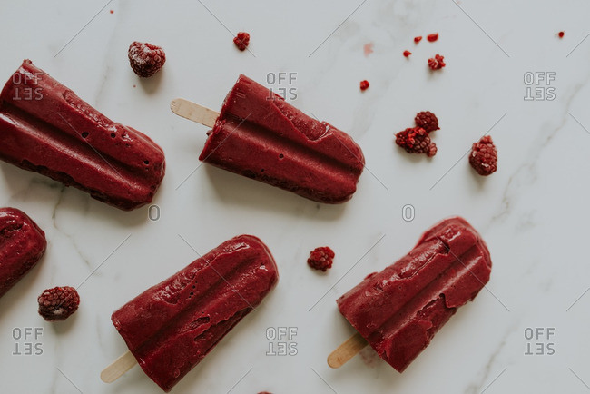 Raspberry flavored popsicles on a marble counter