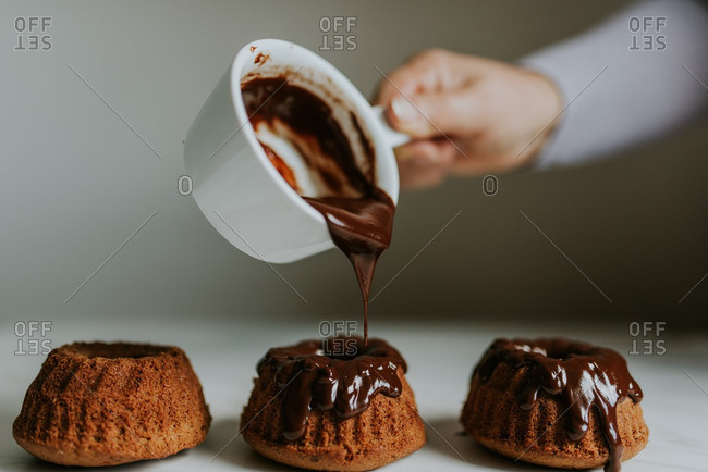 Hand drizzling chocolate onto cupcakes