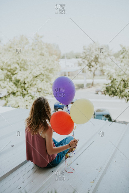 Girl sitting on roof holding balloons