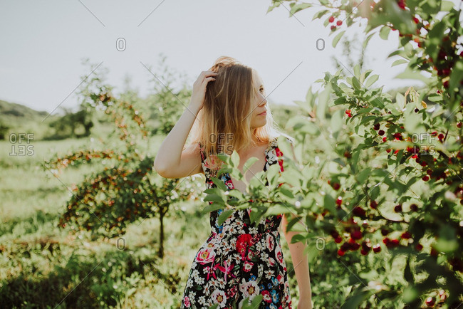 Blonde woman looking at a cherry tree