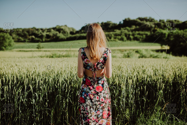Blonde woman looking at a country field