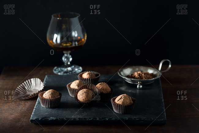 Chocolate truffles on slate tray with glass of liquor