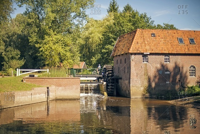 Tourist riding bike by the Berenschot Water mill in the Netherlands